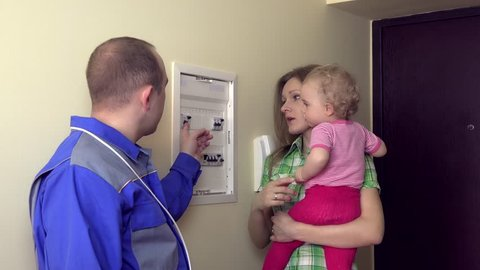 Electrician man explain for housewife woman with small child on hands how to use circuit breaker box cutout. Static shot.