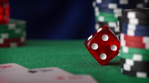 Red dice in sequence rolls, casino chips, cards on green felt