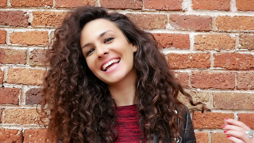 Portrait of happy young woman with beautiful curly hair on a brick wall, slow motion