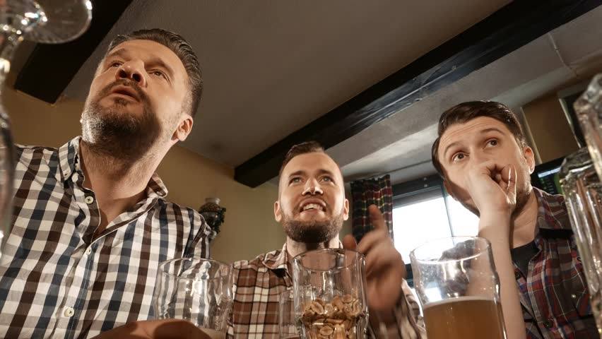 Cheerful old friends having fun watching a football game on TV and drinking draft beer at bar counter in pub 4K UHD video. Nº28   Shutterstock HD Video #16957603
