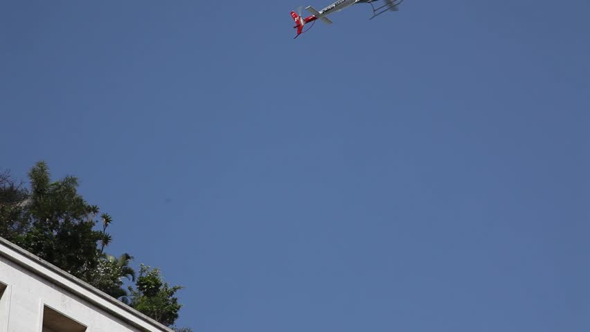 A military police helicopter flies across the sky in San Paulo, Brazil