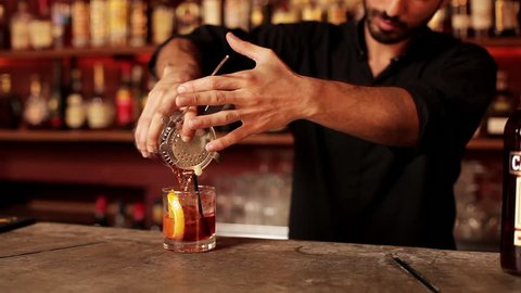 Buenos Aires, Argentina - January 22, 2013: Bartender pouring mixed liqueur into prepared glass through cocktail strainer