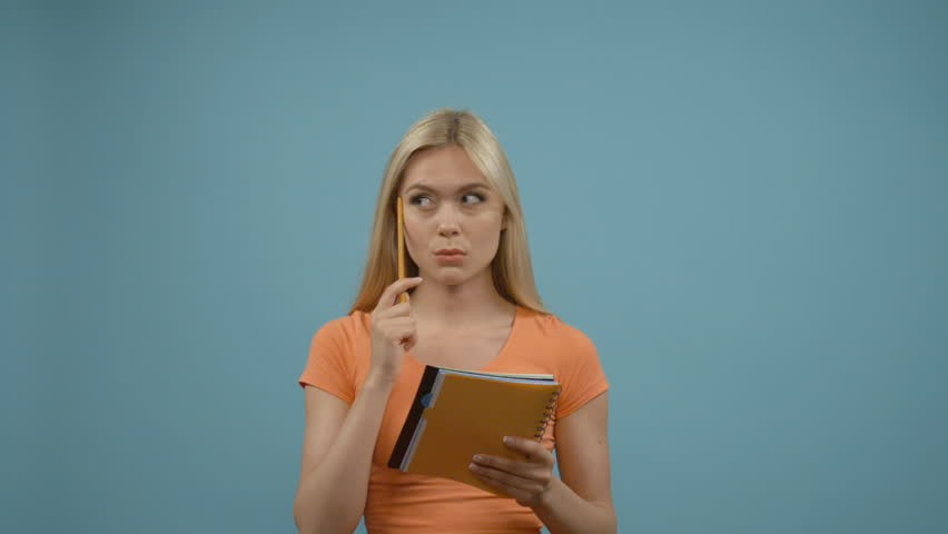 Girl got an idea. Beautiful young blonde woman in orange top pointing away and making notes while standing against blue background.