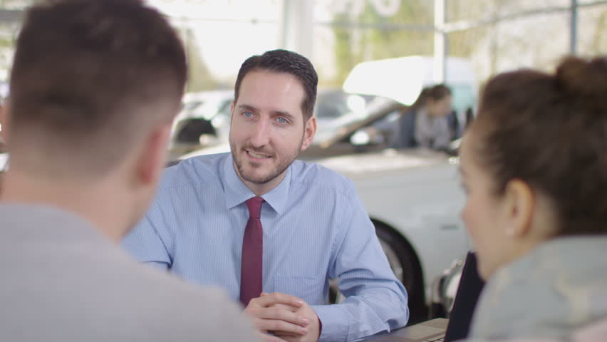 4K Happy couple in car dealers shake hands with salesman & take key to new car UK - April, 2016