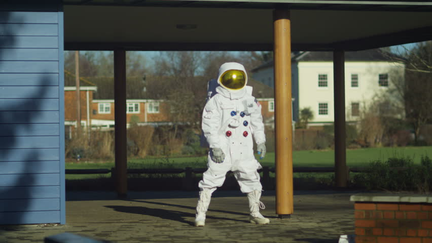 4K Funny astronaut doing stretches and warm up exercises in street. Shot on RED Epic. UK - April, 2016