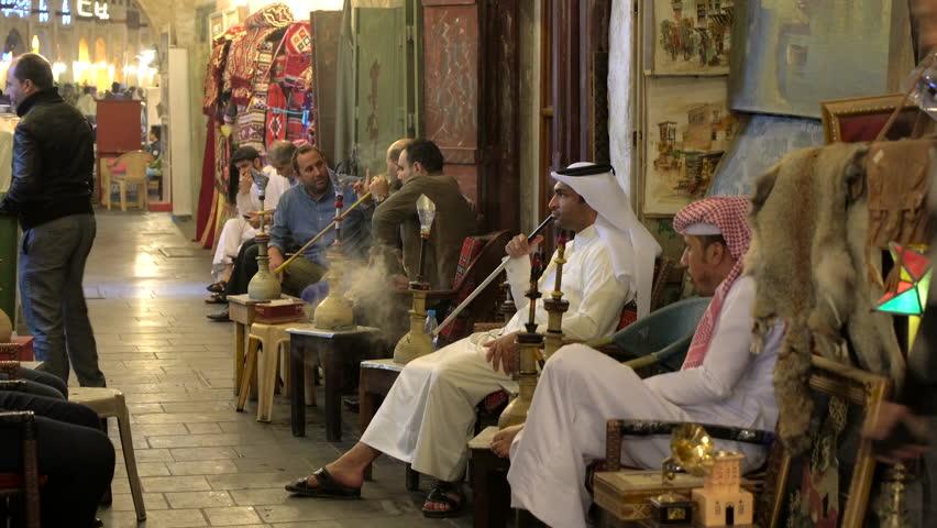 Doha, Qatar - February 2016: Men smoking Sheesha or water pipes in cafe at Souq Waqif, Doha, Qatar
