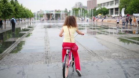 Woman on pink bike are not daring to go through jet of dry fountain in Muzeon park on Crimean embankment.