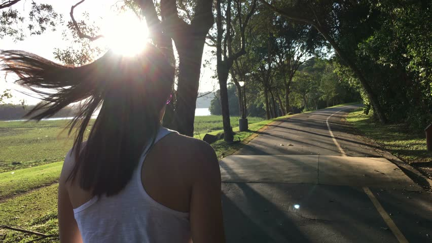 Girl walking by road with sunlight flare hitting lens | Shutterstock HD Video #17052022