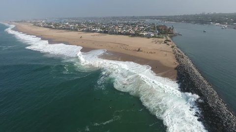 Aerial 4K ultra high definition footage of the world famous Newport Beach Wedge with body boarders in large surf June 2, 2016 - Aerial, elevated perspective view.
