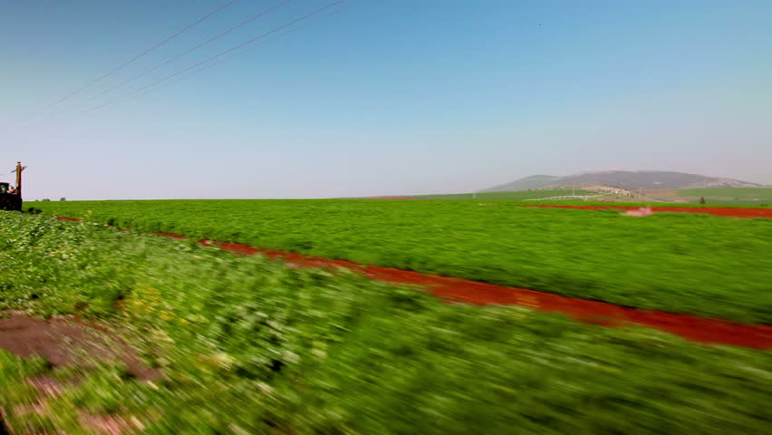 Drive-by in the Ein Harod farmland region of Israel showing a lush green field.  As we move along a tractor is driving in the field that we pass.