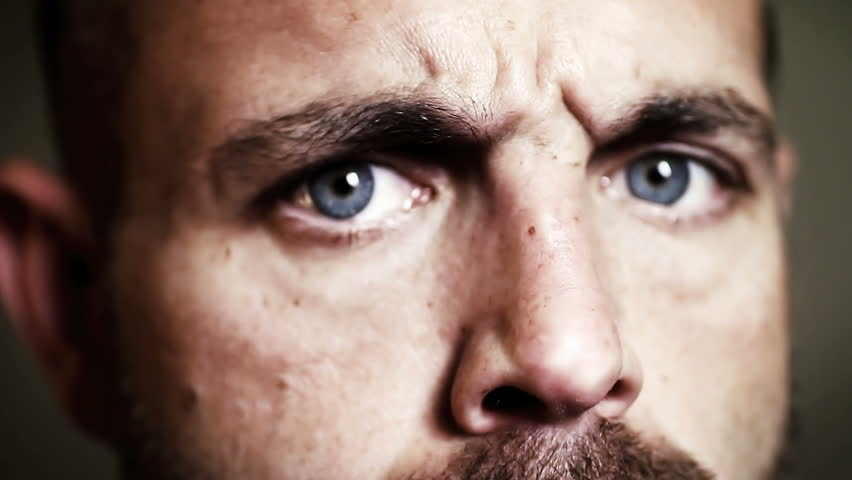 Angry man with evil eyes, serious dramatic expression closeup