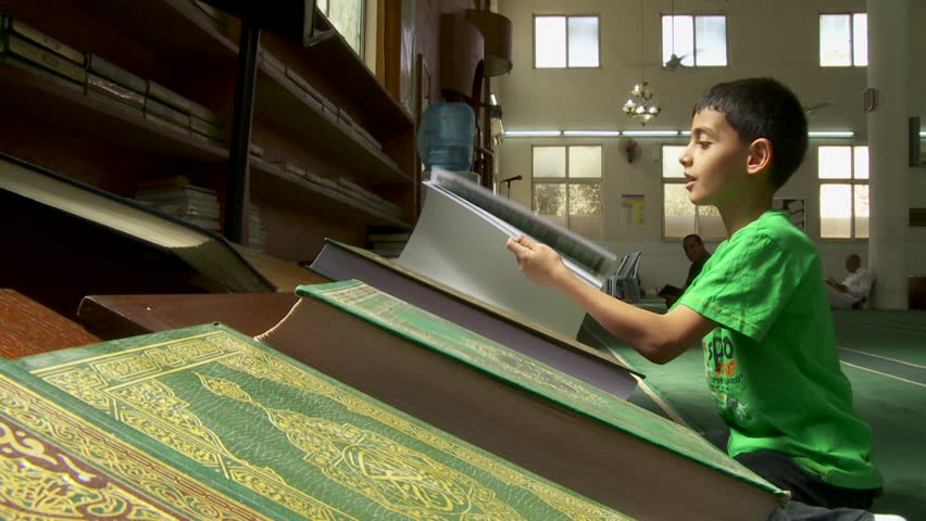 MCU on a Muslim boy in a mosque sitting on his haunches in front of a Quran turning the pages, finding the prayer and reading. (Jordan - 2016)