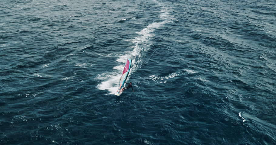 Aerial view of windsurfer gliding across blue ocean, extreme sport | Shutterstock HD Video #17163112