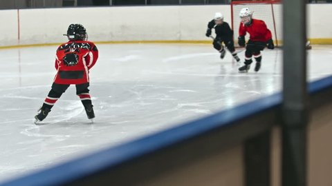 Bunch of kids in professional uniform playing hockey on skating rink