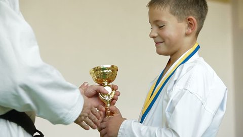 boy receive karate trophy and medal for the victory