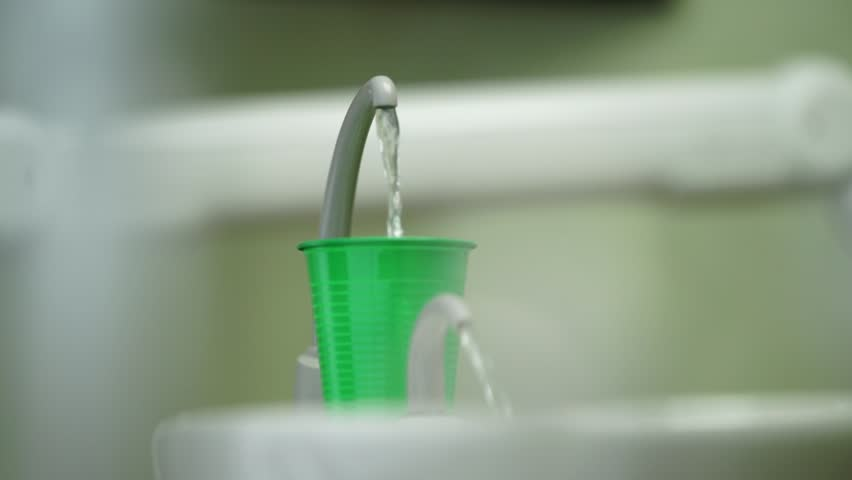 close-up sink with cup of water in the dentist office
