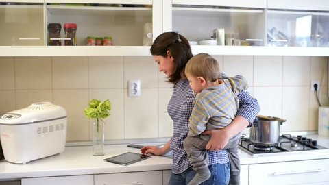 Beautiful young mother holding a baby and doing kitchen work, cooking