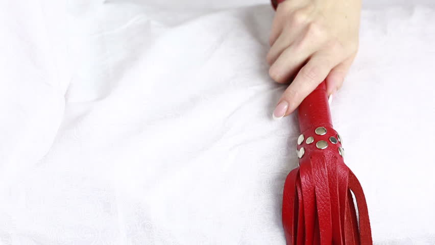 girl takes a red leather whip. sex toys.