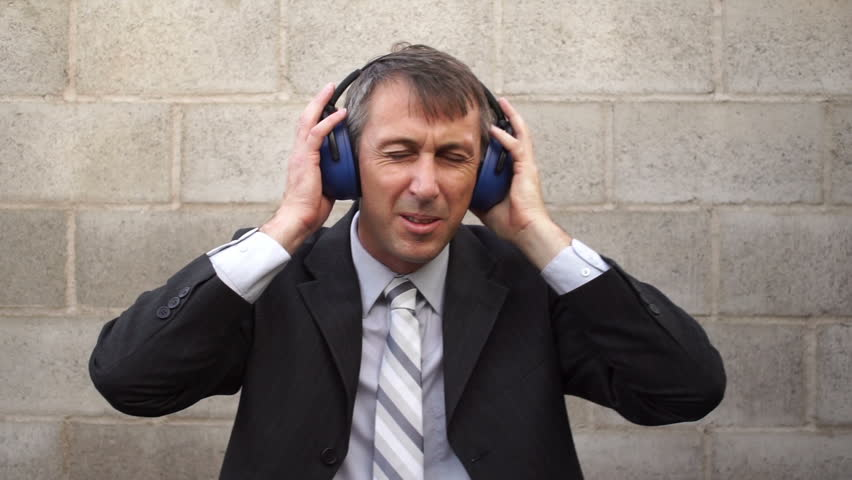 Man wearing a business suit and tie against a cinder-block wall with noise blocking safety acoustic earmuffs  grimacing in pain from loud noises.