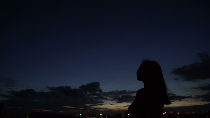 Silhouette of woman looking up at sunset sky with wind blowing hair