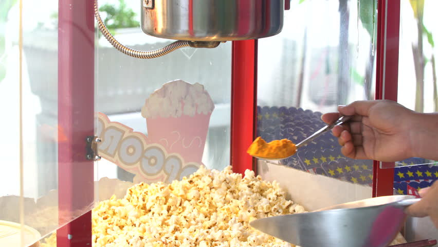 4k a static shot of a commercial popcorn machine mixing by human hand