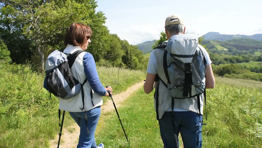 Senior couple on a hiking day looking at map