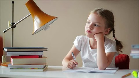 little schoolgirl learns lessons, thoughtful child doing homework, back to school