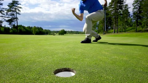 A man putting a golf ball into hole and making a victory gesture before picking up the ball