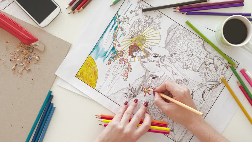 Top view of woman coloring in adult coloring book