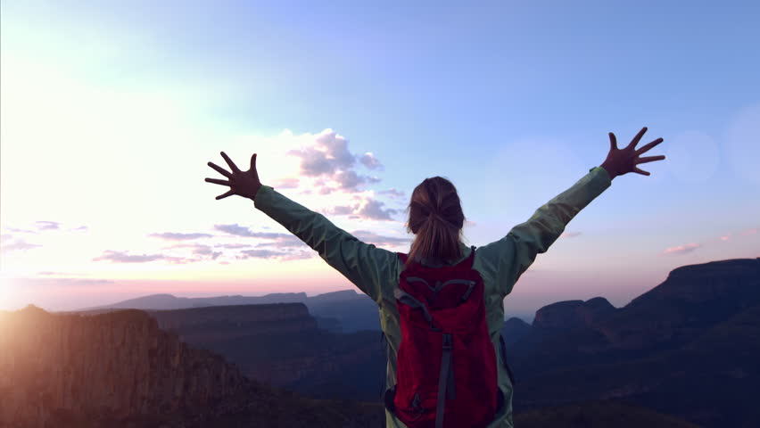 Young independent female hiker with red backpack reaching up top on top of mountain spreading raised arms. Success, inspiration, free, beautiful scenery, winning, motivation. 4K | Shutterstock HD Video #17343505