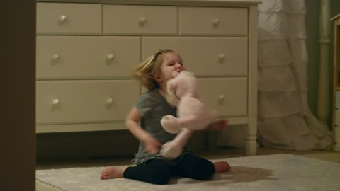 Angry young girl stomps around in her bedroom throwing, hitting and biting a stuffed animal