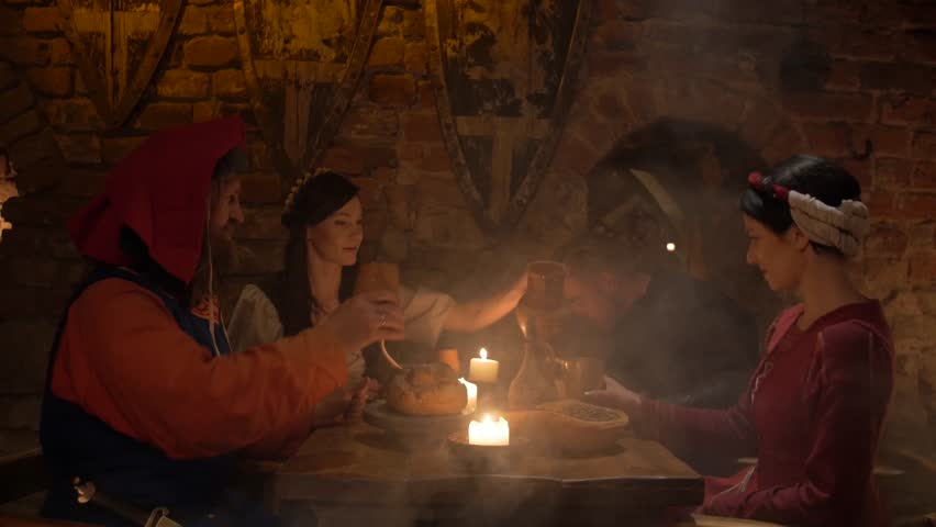 Medieval people eat and drink in ancient castle tavern in 4K UHD video.