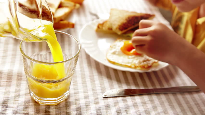 A child's having breakfast (eggs with toast and salad) and orange juice