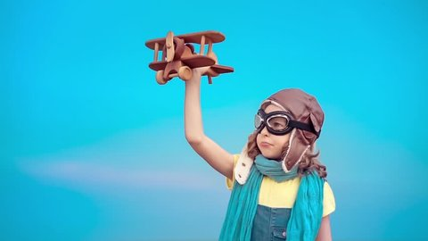 Happy kid with toy airplane. Child having fun outdoors. Kid playing in summer. Child against blue sky background. Travel and vacation concept. Imagination and freedom concept. Slow motion from 120 fps