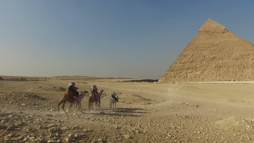 Tourists riding camels at Giza pyramids