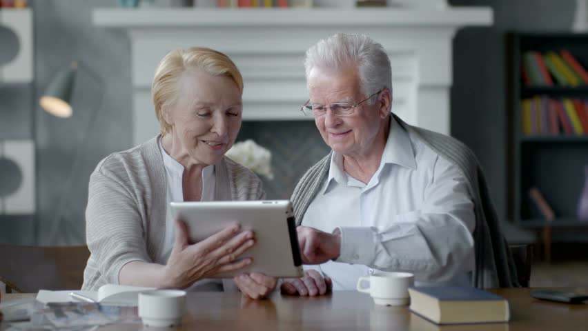 Happy lovely retired couple use tablet computer and laugh
