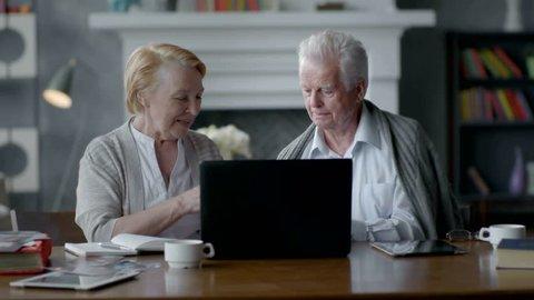 Happy elderly senior couple using laptop computer and smartphone