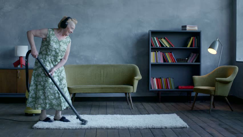 Happy elderly woman listening music on headphones and dancing with a vacuum cleaner, home fun | Shutterstock HD Video #17493787