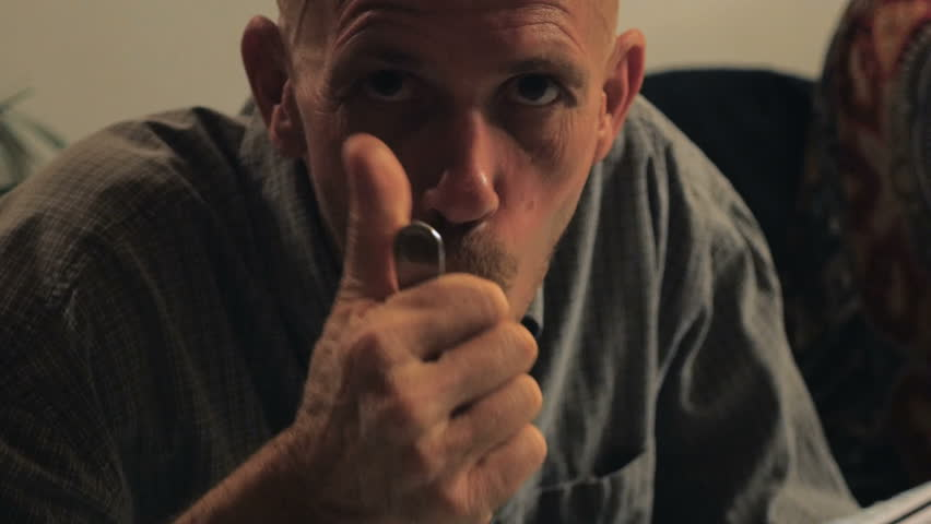 A bald man with a goatee gives the thumbs up while eating and chewing food at a dinner table in the evening