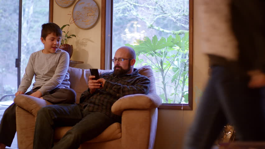 A father and son sit and talk on a couch at home while the dad uses his phone | Shutterstock HD Video #17512612
