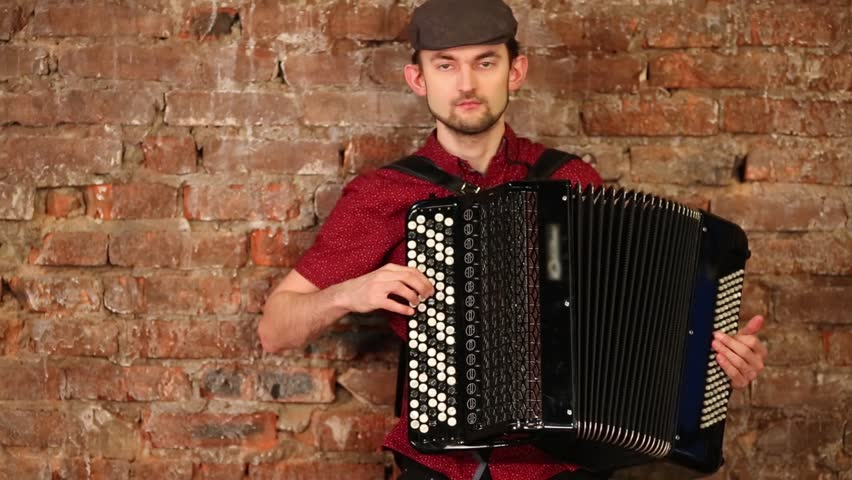 Man in hat and red shirt with spots playing accordion near brick wall.