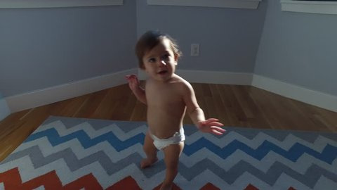 baby learning to walk and falling down on a colorful rug
