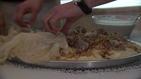 Mansaf. A chef peels back Markouk bread to reveal a dish of lamb cooked in yoghurt and served on a bed of rice. Mansaf is the national dish of Jordan. (Jordan - 2016)