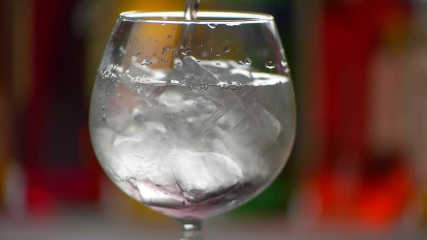 Liquid slowly pouring in glass. Cubes of ice in beverage. Imported gin for tom collins. Traditional recipe of tasty cocktail.