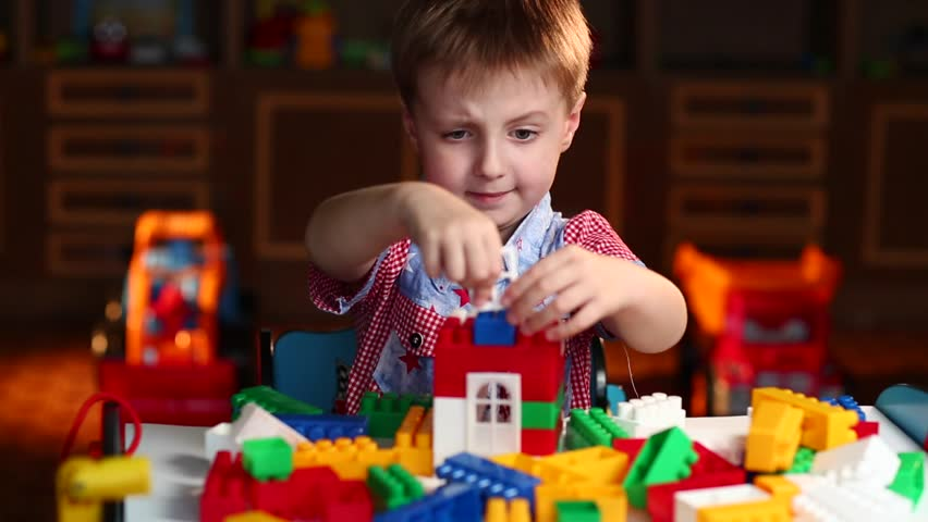 Boy Builds a House Out of Colored Blocks of Lego at the Table