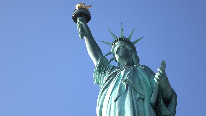 Statue of Liberty in bright sunlight on sunny day 4k Top half of Lady Liberty in front of beautiful clear blue sky. | Shutterstock HD Video #17543122