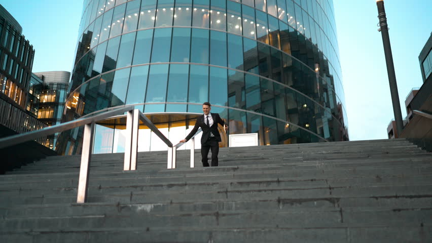 Young successful businessman easy sliding on the outdoor stairs rail with smile and jump at the end. Glossy business centre building at the background. Teal and Orange style. Wide 4k tripod shot.