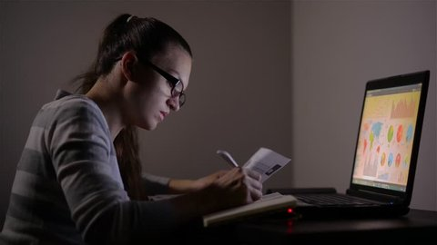 Young female business woman working at home, She works late into the night looking at monitor, Beautiful student preparing for the exam at night, girl studying at the night