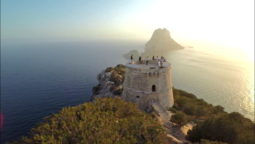 Aerial view of Torre del Pirata, an old tower on the top of a cliff, in front of the islet of Es Vedra, in the island of Ibiza, with a beautiful sunset.