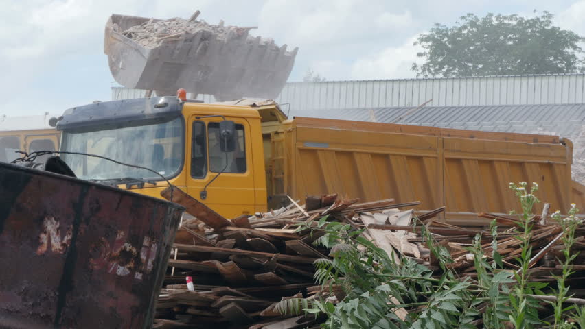 Bulldozer charging shovel with broken bricks and other rubble and loading in truck trailer. Demolition of factory building. Machinery in action, machines working on construction site. #17619550